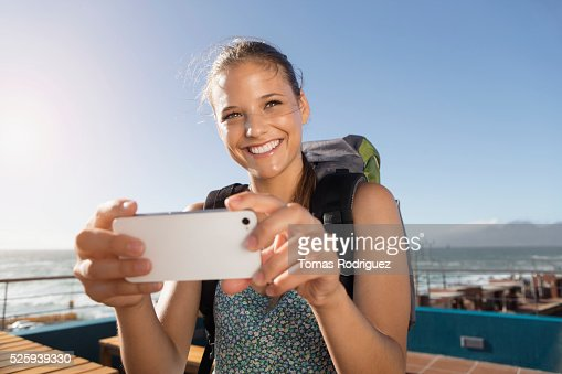 Portrait of young woman with backpack and smartphone : Photo