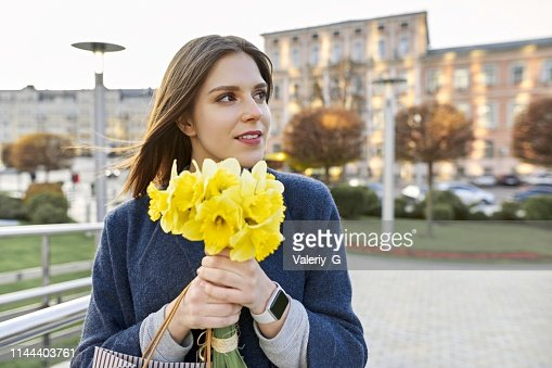 Portrait of young woman with bouquet of yellow spring flowers daffodils. Beautiful girl close up, spring city background : Stock Photo