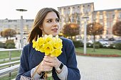 Portrait of young woman with bouquet of yellow spring flowers daffodils. Beautiful girl close up, spring city background.