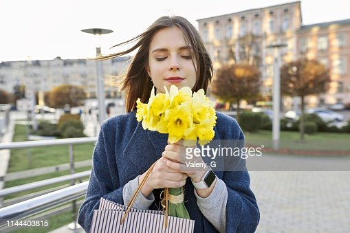 Portrait of young woman with bouquet of yellow spring flowers daffodils. Beautiful girl in city enjoys flowers, eyes closed. : Stock Photo