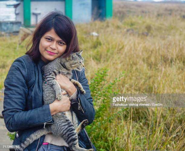 Portrait Of Young Woman With Cat Standing On Grassy Field
