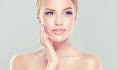 Young  blond-haired woman with clean fresh skin and soft, delicate make up. Woman  is touching tenderly to own face. Image of freshness and cleanliness.Cosmetology, plastic surgery,facial treatment an