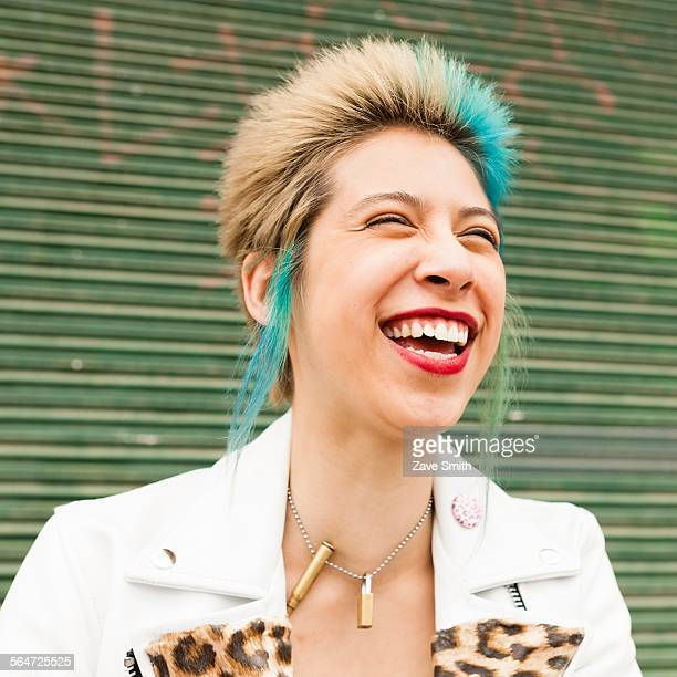 Portrait of young woman with colourful hair, laughing, outdoors