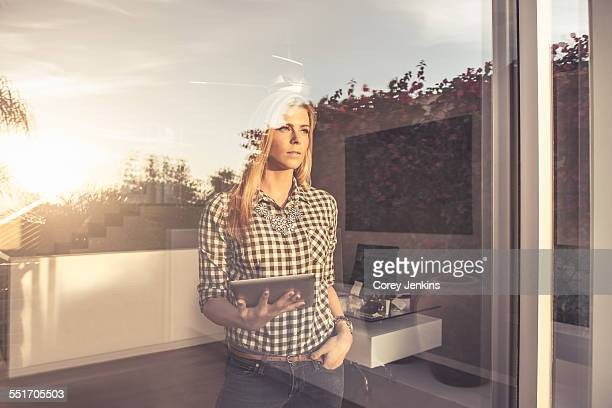 Portrait of young woman with digital tablet gazing from suburban window