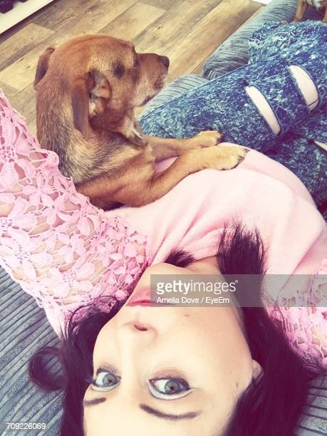 Portrait Of Young Woman With Dog Resting On Sofa