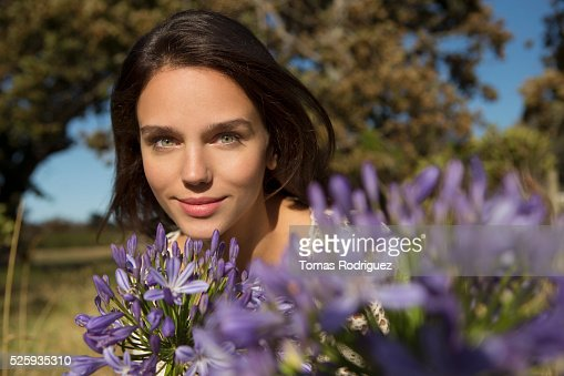Portrait of young woman with flowers in front : Stock Photo