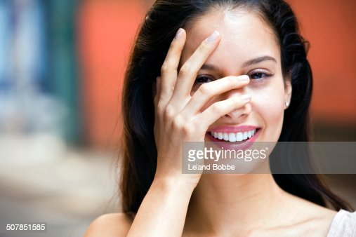 Portrait of young woman with hand covering face