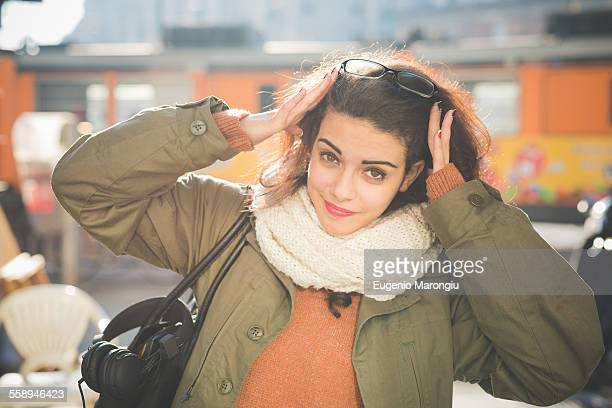 Portrait of young woman with hands in hair on railway platform