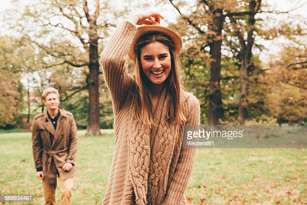 Portrait of young woman with hat in autumnal park with boyfriend in the background