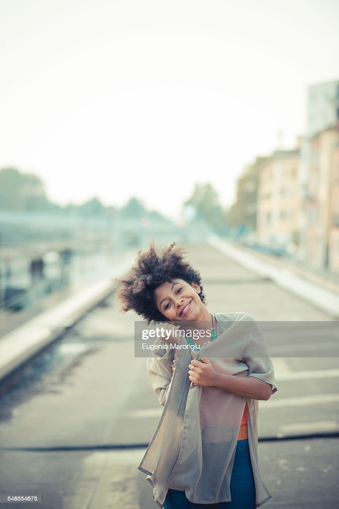 Portrait of young woman with head cocked in city industrial area