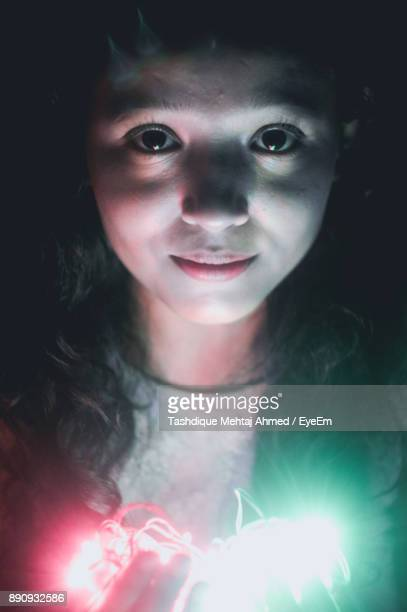 Portrait Of Young Woman With Illuminated Lights In Darkroom