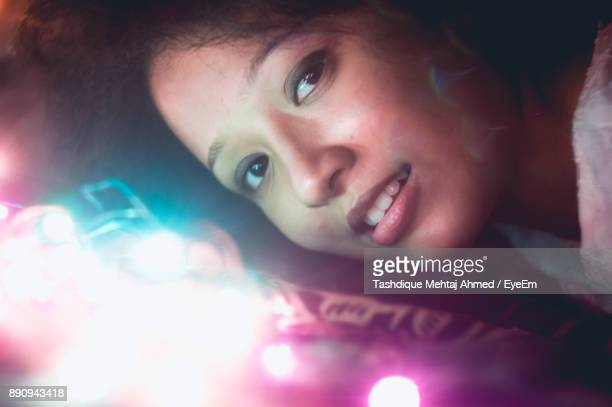 Portrait Of Young Woman With Illuminated Lights On Bed