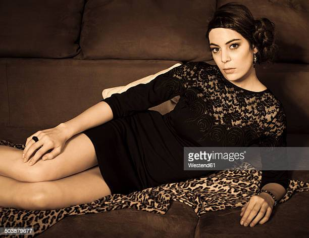 Portrait of young woman with little black dress lying on couch