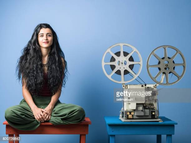Portrait Of Young Woman With Long Black Hair Posing With Film Projector
