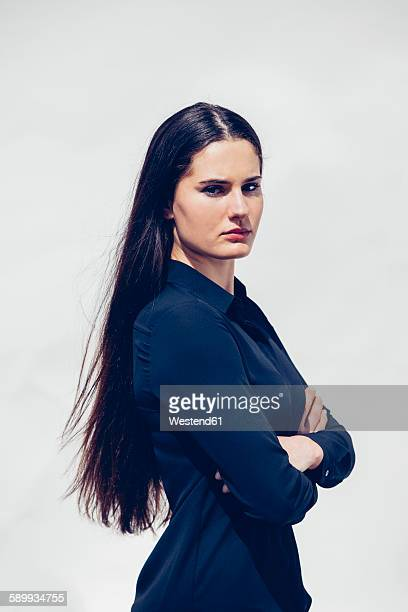 Portrait of young woman with long dark hair wearing blue blouse in front of white background