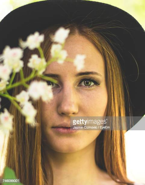 Portrait Of Young Woman With Long Hair Wearing Hat By Flowers