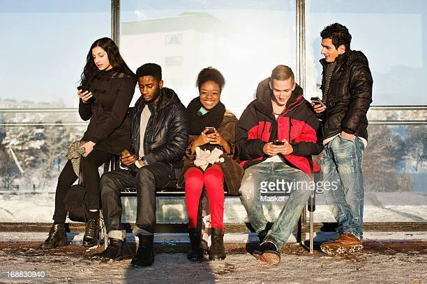 Portrait of young woman with multi ethnic friends using mobile phones on bench