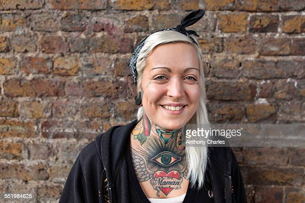 Portrait of young woman with nose ring stud and tattoo