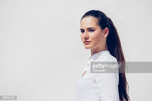 Portrait of young woman with ponytail wearing white blouse in front of white background