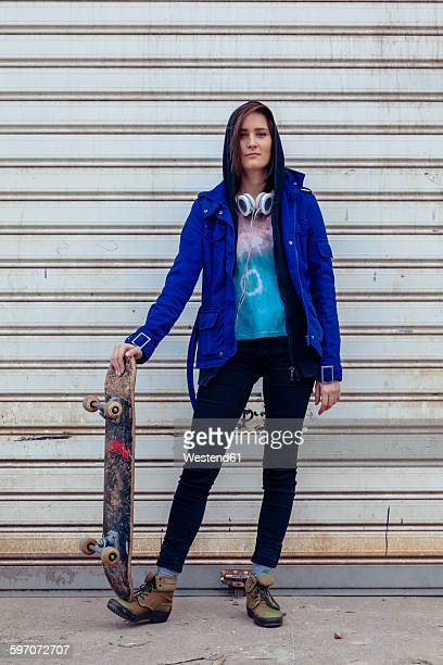 Portrait of young woman with skateboard