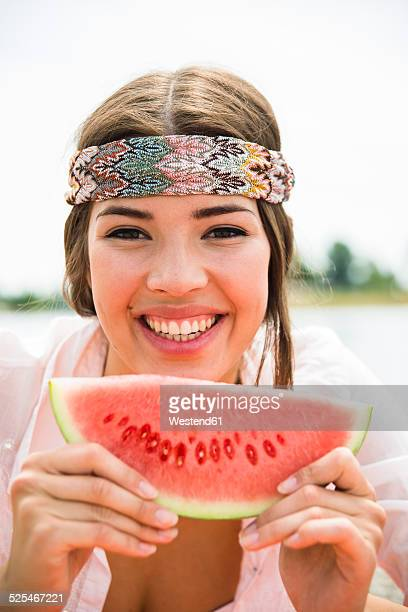 Portrait of young woman with slice of watermelon on the beach