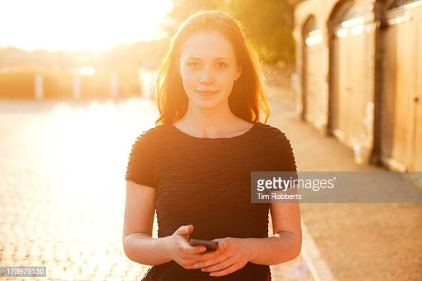 Portrait of young woman with smart phone at sunset