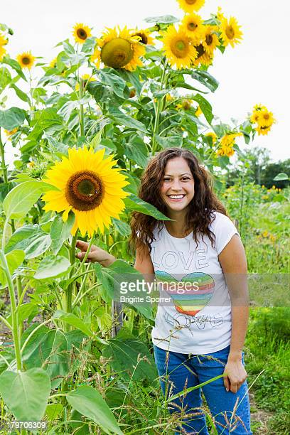 Portrait of young woman with yellow sunflowers in allotment