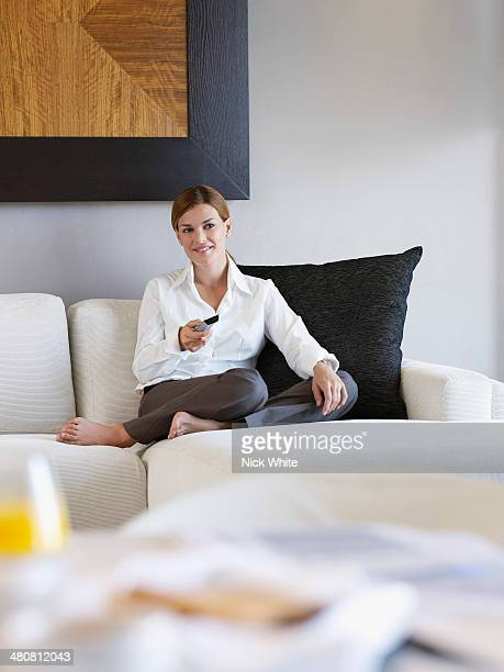 Portrait of young woman working with remote control in hotel room