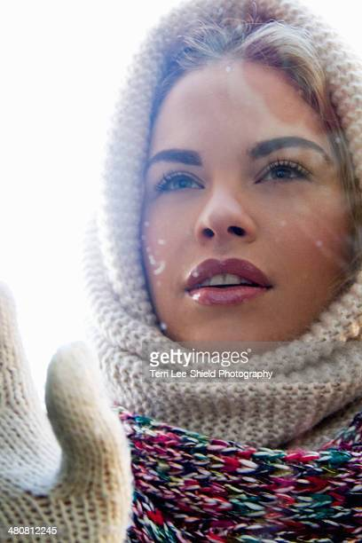 Portrait of young woman wrapped up looking through window