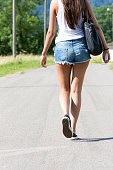 Portrait of young woman wwearing hot pants walking on road