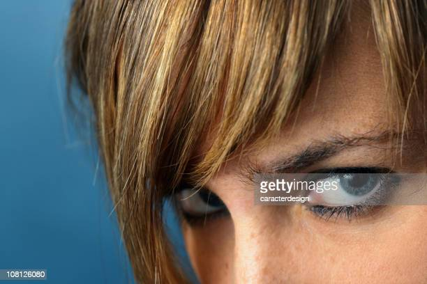 Portrait of Young Woman's Eyes Glaring, On Blue Background