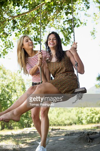 Portrait of young women on swing : Bildbanksbilder