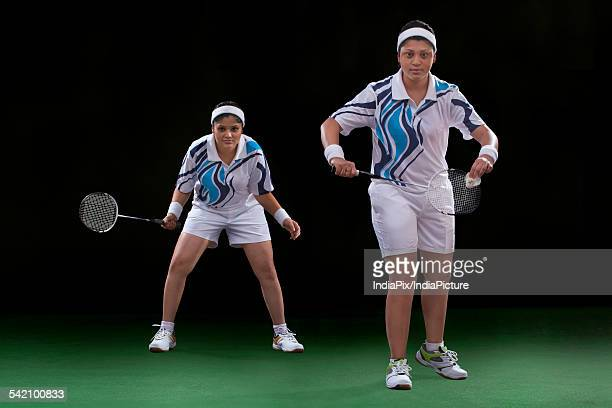 Portrait of young women playing badminton over black background