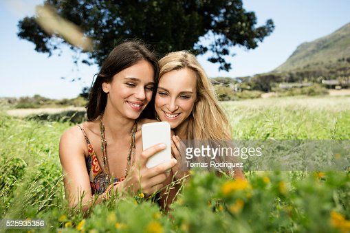 Portrait of young women using cell phone : Stock Photo