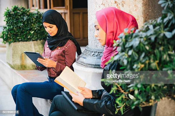 Portrait Of Young Women Wearing Headscarf Reading Books Outdoors