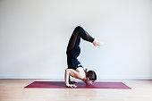 Portrait of young yogi woman practising yoga, wearing black sportswear, white studio background, chinstand scorpion pose (selective focus)