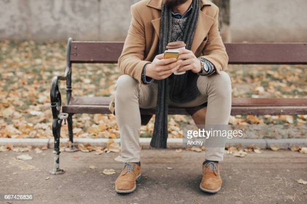 Portrait of yuccie man sitting on the bench in the park
