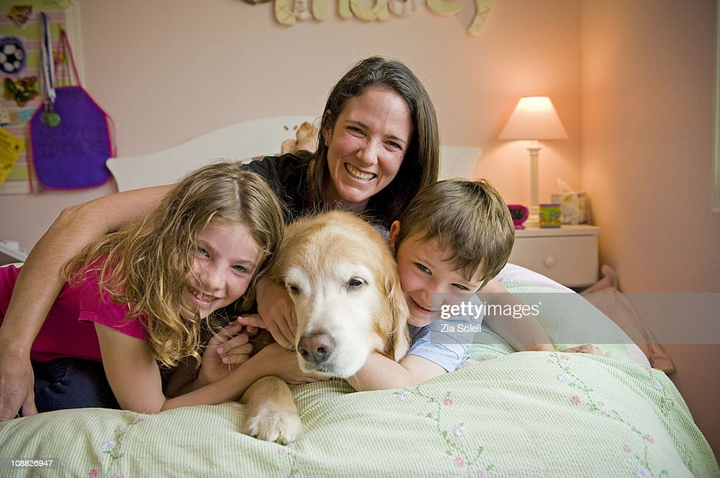 portrait on their bed, Mom, dog, son and daughter : Stock Photo