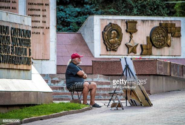 A portrait painter waits for tourists next to a World War II victims monument in Volgograd on August 21 2017 Volgograd Arena will host several cames...