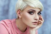 Portrait of young female model in fashionable make up with short hair looking at camera