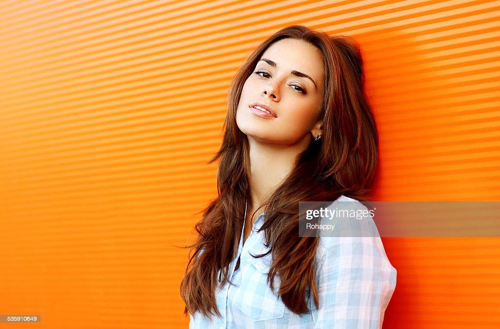 Retrato bonito sensual mulher ao ar livre contra parede colorido em : Foto de stock