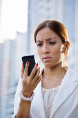 Businesswoman with disappointed expression using mobile phone in city street, receiving bad news via email
