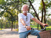 Portrait, Senior man on cycle ride in the park