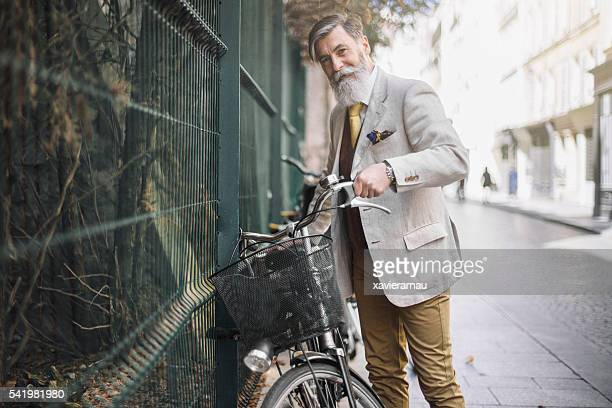 Portrait senior man picking his bicycle in the street