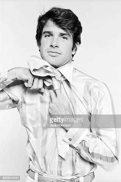 Portrait series of actor Warren Beatty as he knots his necktie late 1960s or early 1970s