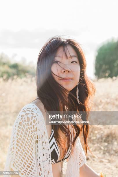 Portrait serious boho woman in bikini in sunny field