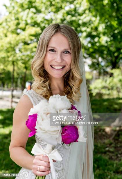 portrait shot of a happy smiling bride with long blonde hair wearing her white wedding dress on her sunny wedding day and holding the bridal bouquet of flowers consisting of white and pink peonies in her right hand - green trees out of focus in background