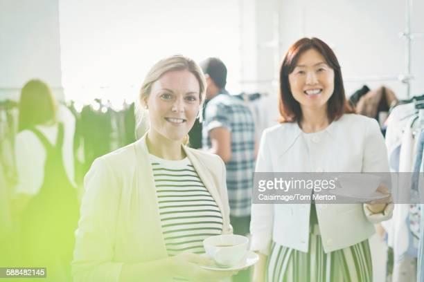 Portrait smiling fashion designers drinking tea