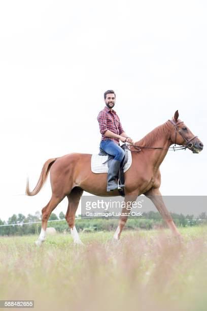 Portrait smiling man horseback riding in rural field