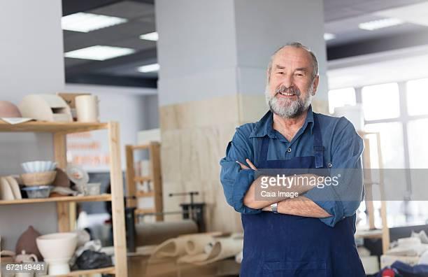 Portrait smiling senior man in pottery studio